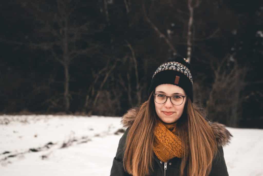 Mulher branca de roupas de frio na neve.