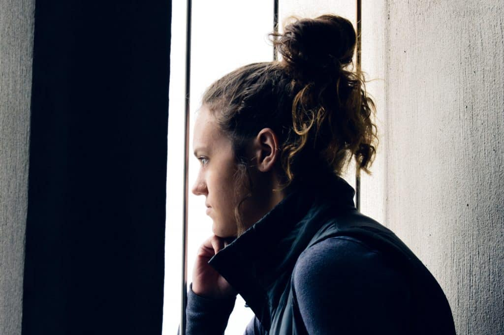 Mulher olhando para fora da janela pensativa