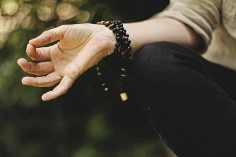 Mão branca feminina com o indicador e polegar encostados.