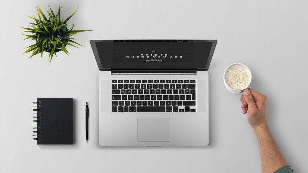 Imagem de uma mesa de trabalho super organizada e limpa. Sobre ela um pequeno vaso de planta, uma agenda e uma caneta na cor preta,  um notebook e a mão de um homem segurando um caneca branca com leite e café.