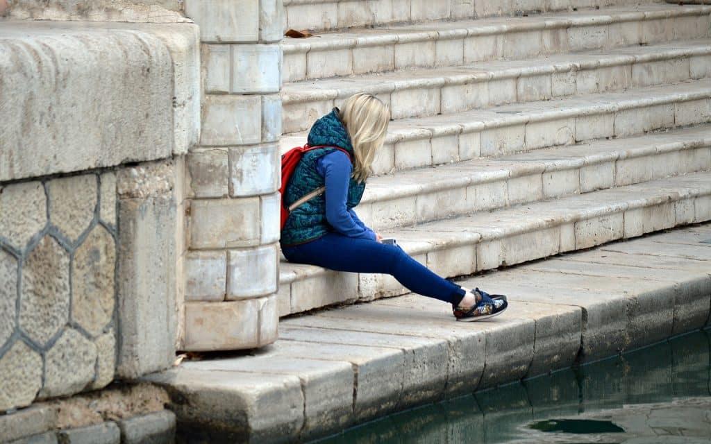 Imagem de uma jovem gatora de cabelos loiros, toda agasalhada e com uma mochila vermelha nas costas. Ela está sentada em uma grande escadaria. Está cabisbaixa e se sentindo culpada por ter feito algo.