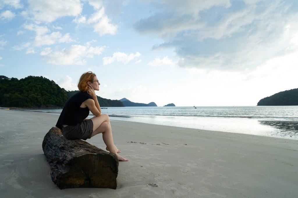 Imagem de uma mulher solitária sentada em um tronco disposto na areia de uma praia deserta. Ela usa uma bermuda e uma camiseta azul e está olhando para o mar.