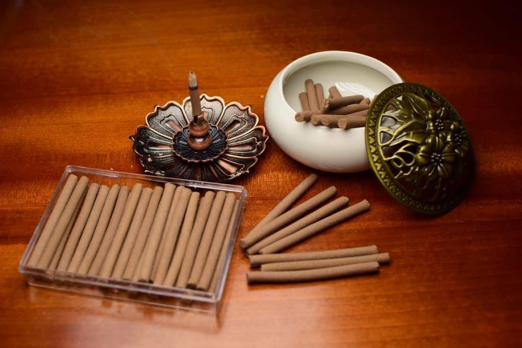 Imagem de uma caixa de incenso de ananda, ao lado um incensário com um incenso sendo queimado e ao lado um suporte redondo com tampa contendo alguns incensos apagados.