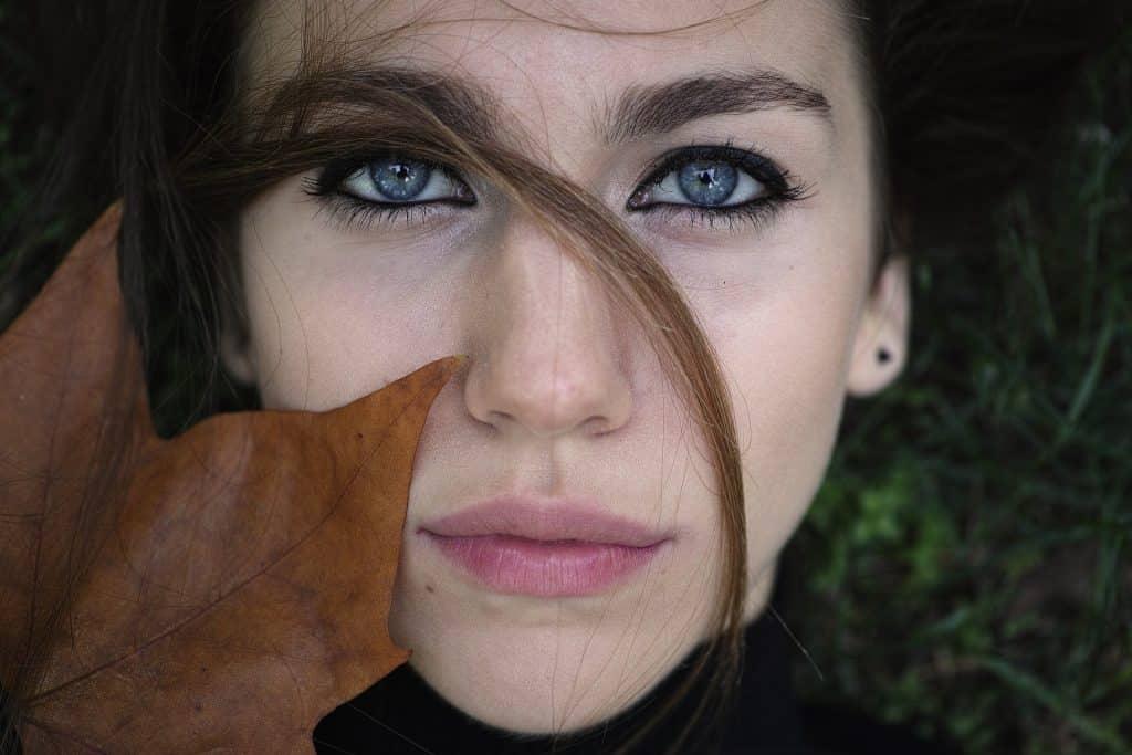 Imagem do rosto de uma modelo de pele branca, olhos azuis e lábios cor de rosa. Ela está deitada sobre um gramado e sobre o rosto dela uma folha de outono na cor marrom.