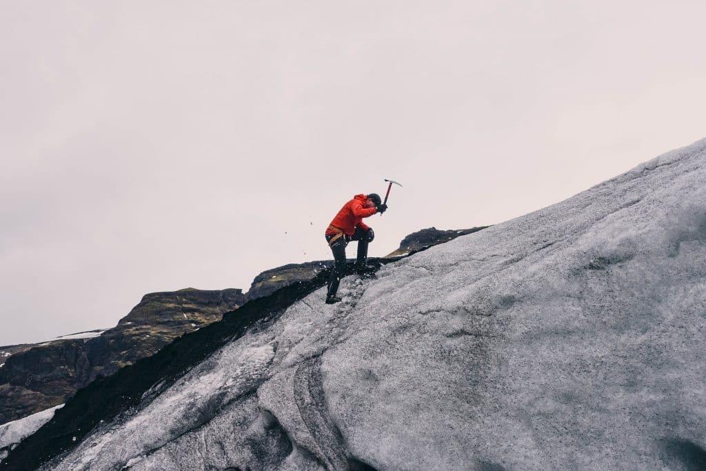 Imagem de um homem vestido com roupa apropriada para o inverno rigoroso. Ele está escalando uma montanha coberta com neve. Em uma das mãos ele segura uma picareta.