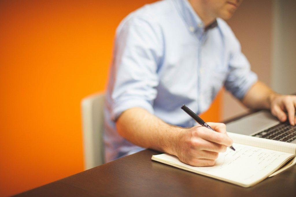 Imagem de um jovem em seu escritório. Ele está sentando em sua cadeira em frente ao notebook. Ao lado ele tem um cadern onde também faz algumas anotações.