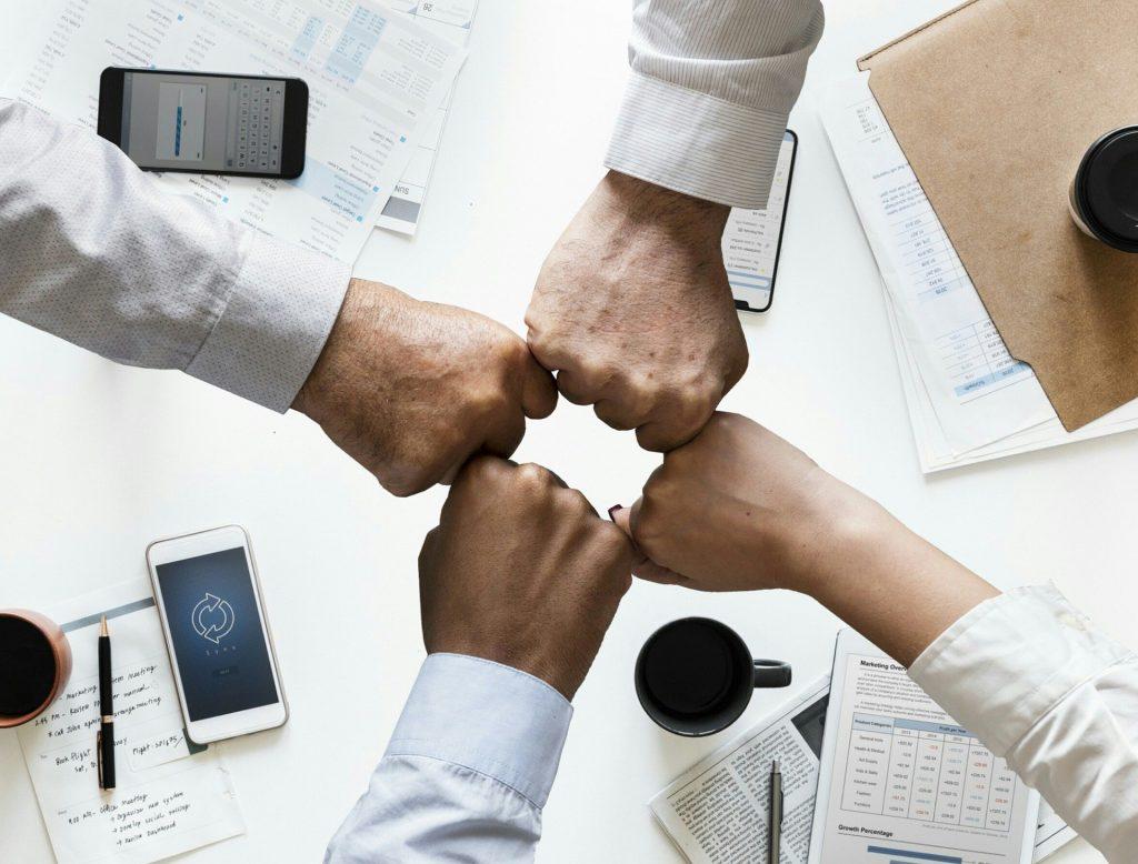 Imagem de quatro mãos fechadas, sendo três masculinas e uma feminina. Elas estão sobre uma mesa de trabalho contendo alguns papéis, celulares, canetas e xícaras de café.