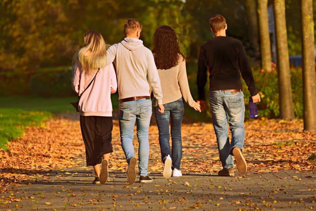 Imagem de dois casais sendo que um deles está de mãos dadas e o outro está abraçado. Os dois homens e uma das mulheres usam calças jeans e blusa de frio e a outra usa uma calça preto mais curta e um moletom rosa. Os quatro caminham por uma calçada cheia de folhas de árvore por conta do outono.
