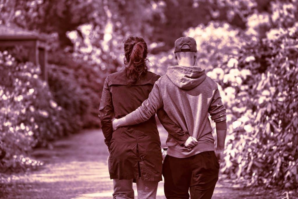 Imagem preta e branco de um casal de costas caminhando abraçados por uma trilha arborizada. Ambos usam roupas de inverno.