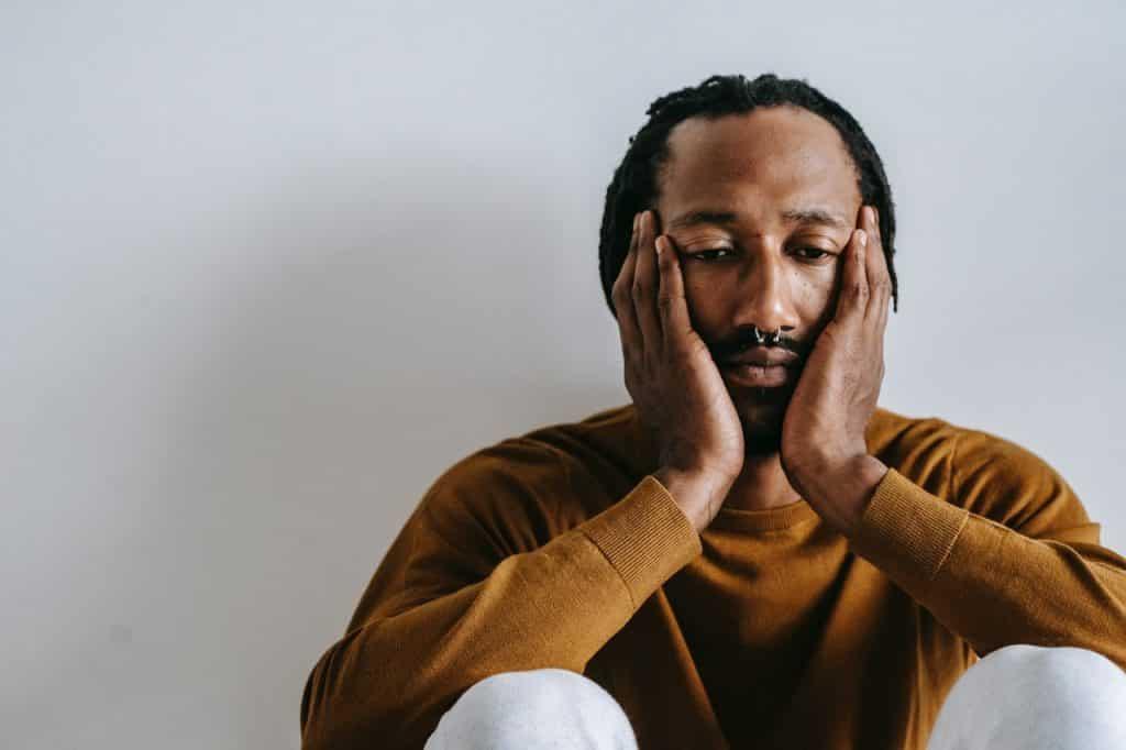 Homem negro sentado no chão com as mãos no rosto com feição de tristeza.