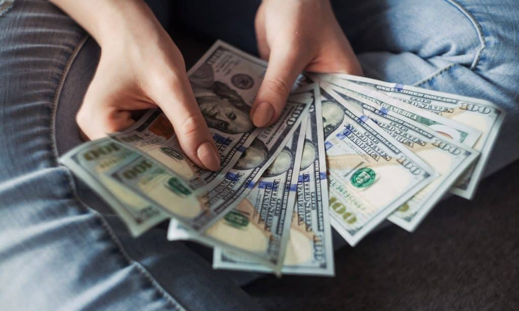 Mãos seguram notas de dólares.