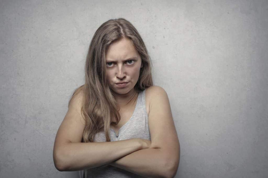 Mulher com semblante raivoso e de braços cruzados.