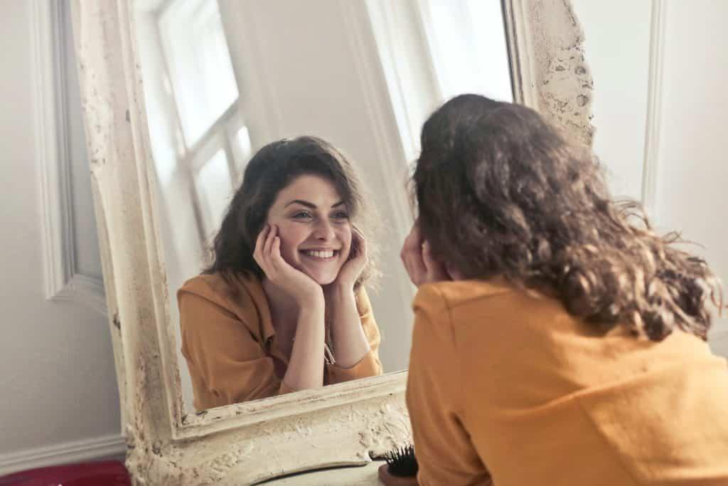 Mulher sorrindo olhando para o espelho