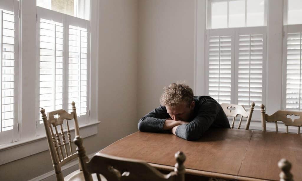 Homem apoia o corpo sobre uma mesa. Seu rosto está sobre os próprios braços e ele tem o semblante entristecido.