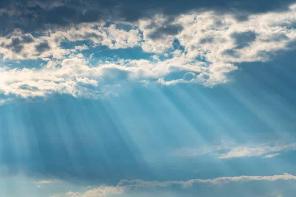 Sob céu azul, nuvens e raios solares.