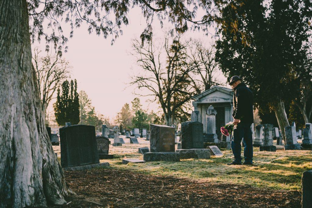 Homem de roupa preta com um buquê de flores na mão no cemitério.