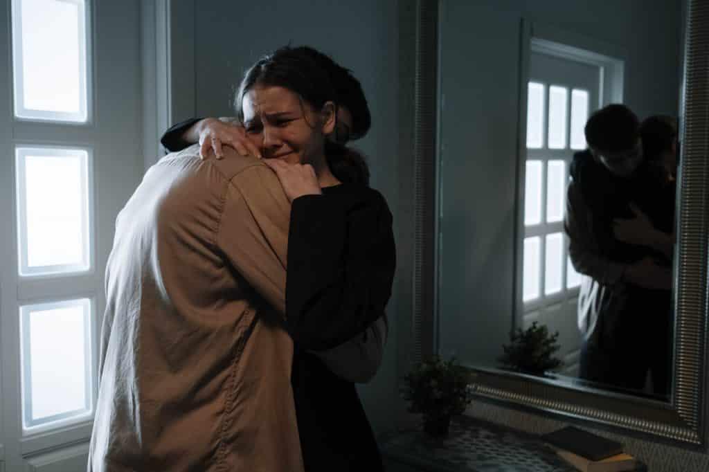 Um homem e uma mulher chorando abraçados pela morte de alguém.