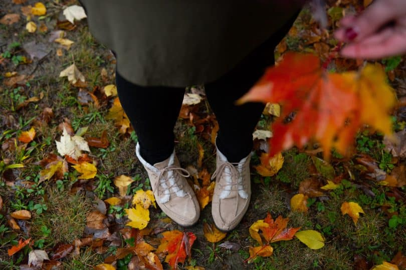 Pés de alguém em um gramado com folhas de outono