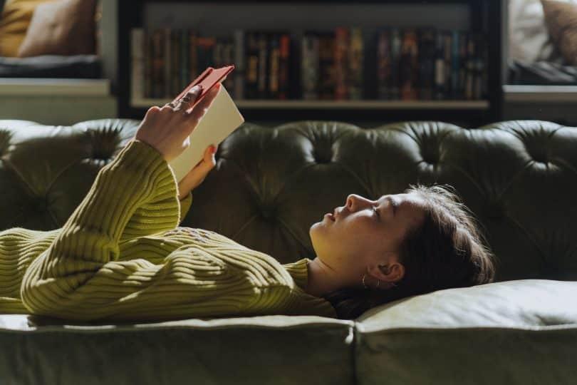 Mulher deitada em um sofá lendo um lviro