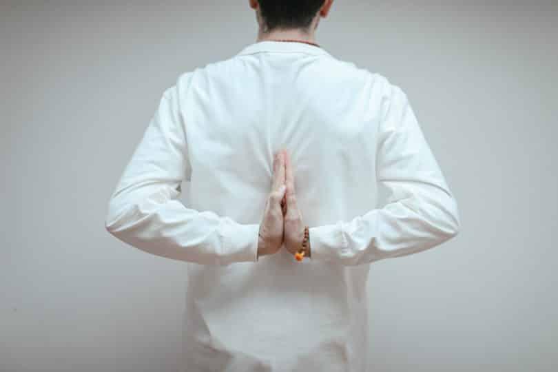 Homem posicionando suas mãos nas costas