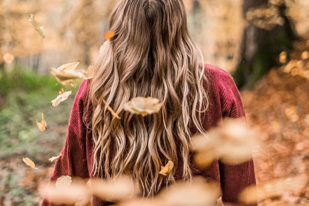 Mulher de costas entre folhas secas características do outono.