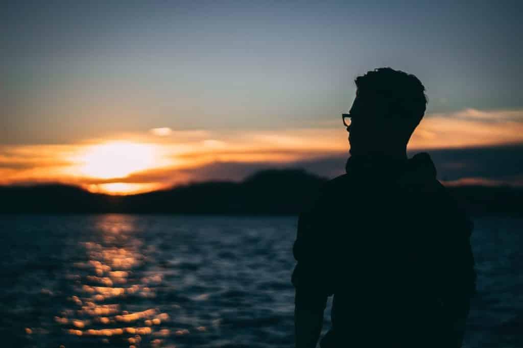 Silhueta de homem voltada ao mar e, ao fundo, ao pôr do sol.