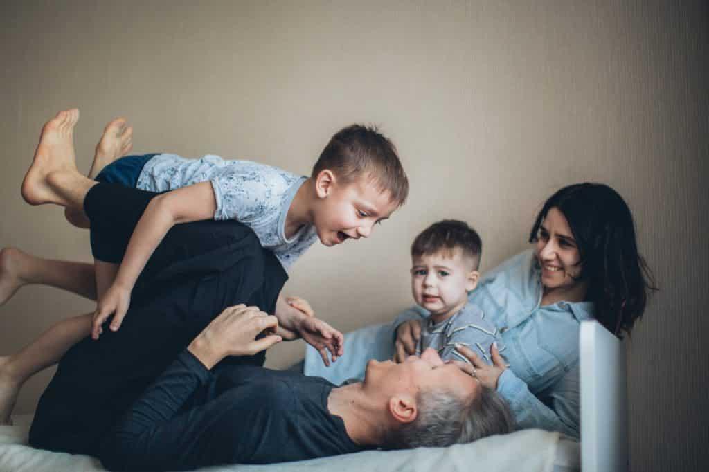 Pais brincando com os dois filhos pequenos no sofá.