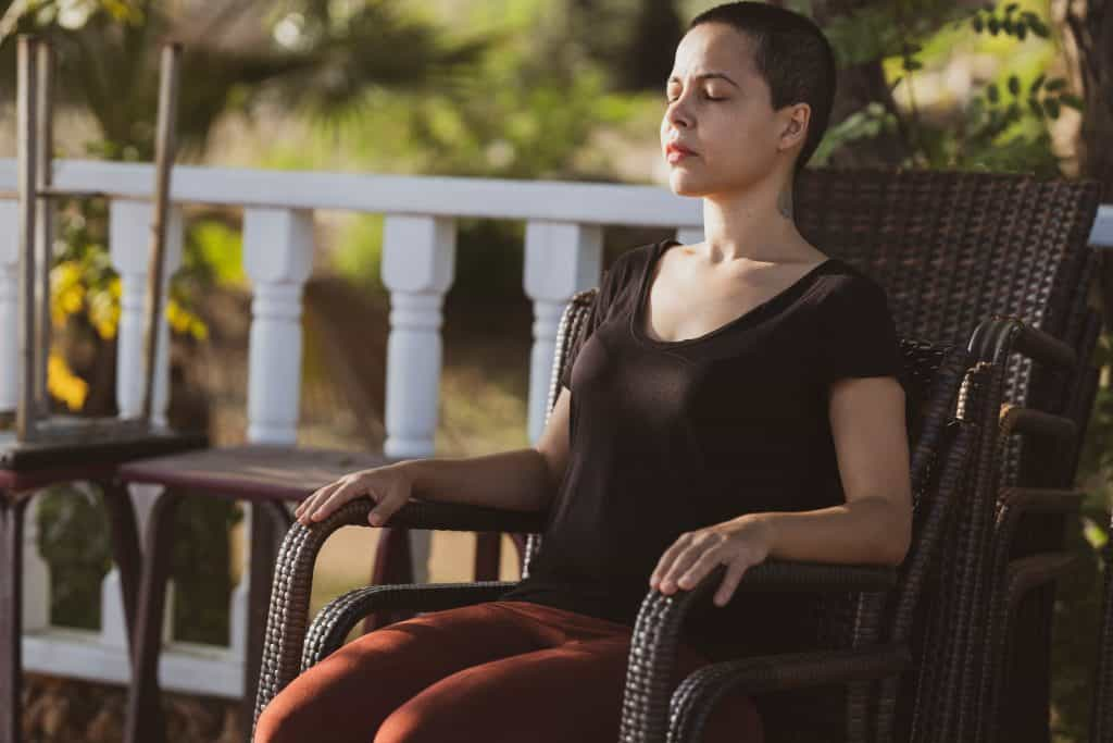 Mulher sentada na cadeira de olhos fechados