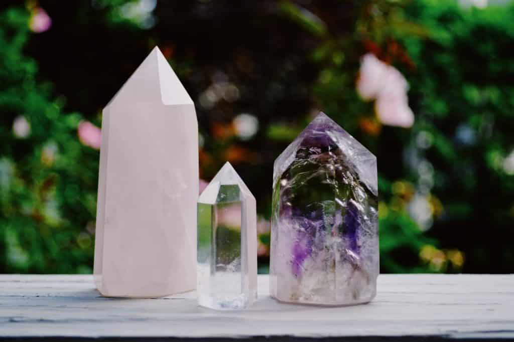Três cristais diferentes posicionados sobre superfície de madeira. Ao fundo, há área externa bucólica.