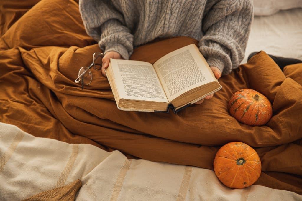 Pessoa sentada na cama com cobertor, segurando livro aberto
