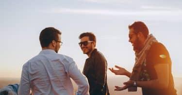 Três amigos conversando um ao lado do outro