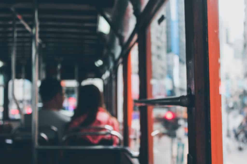 Interior de ônibus. Ao fundo, em desfoque, há duas pessoas sentadas em dois dos bancos.