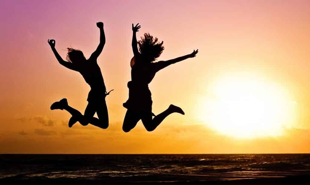 Duas silhuetas femininas pulam com os braços e pernas erguidos.