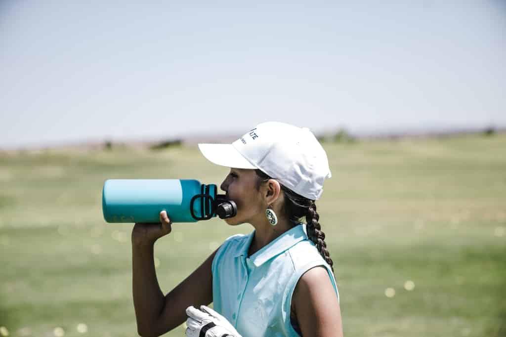 Mulher bebe água em cenário externo.