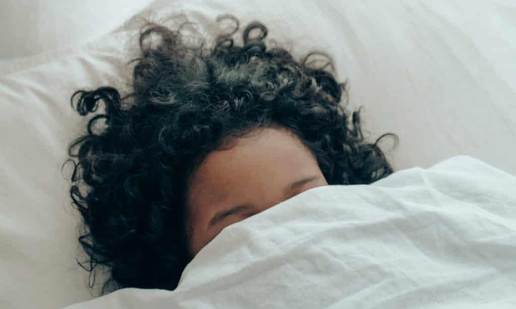Menina dorme com tecido sobre o rosto.