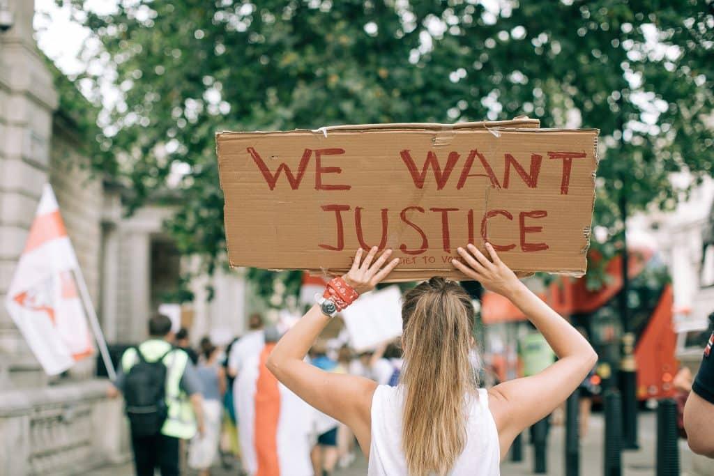 """Mulher segurando cartaz escrito """"Nós queremos justiça"""""""