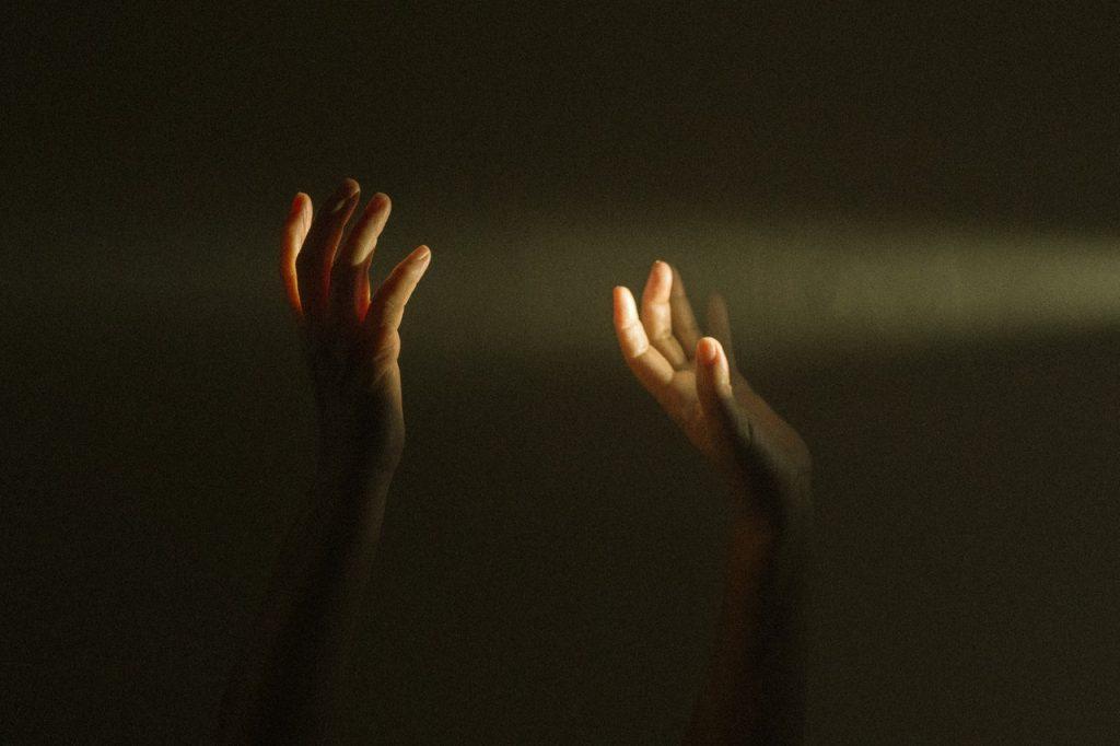 Mãos brancas levantadas.