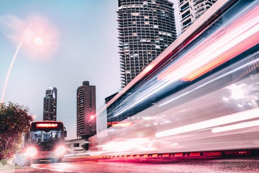 Ônibus em ambiente urbano. À direita, efeito de luzes em movimento.