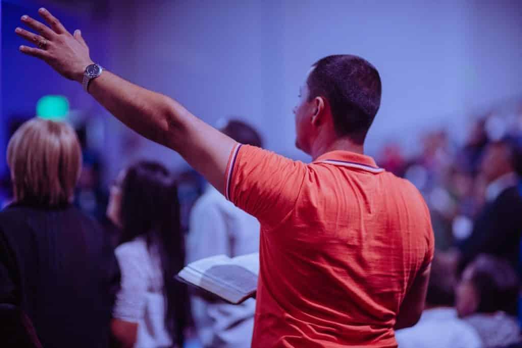Homem branco de costas segurando bíblia e a outra mão levantado.