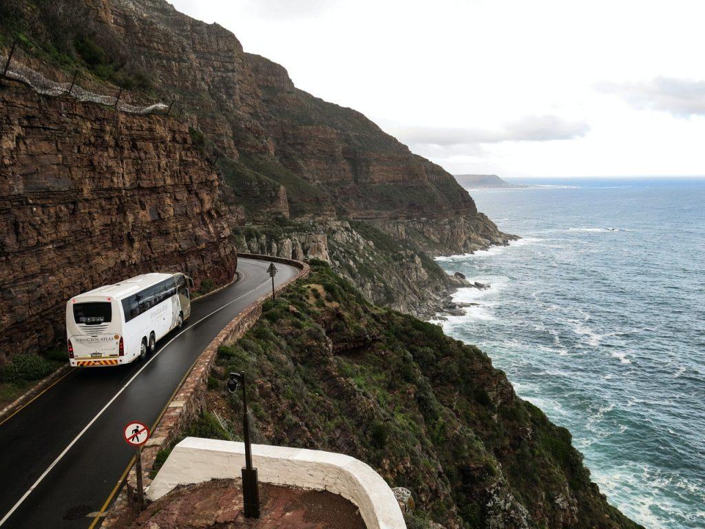 Ônibus em estrada à beira de penhasco.