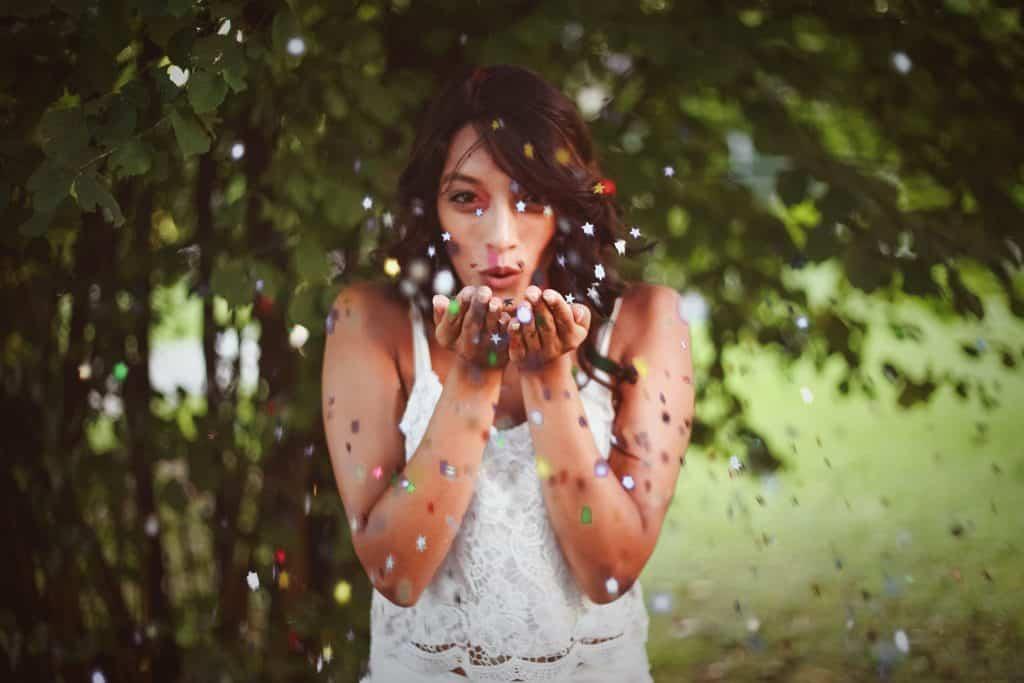 Mulher assoprando confetes de estrelas