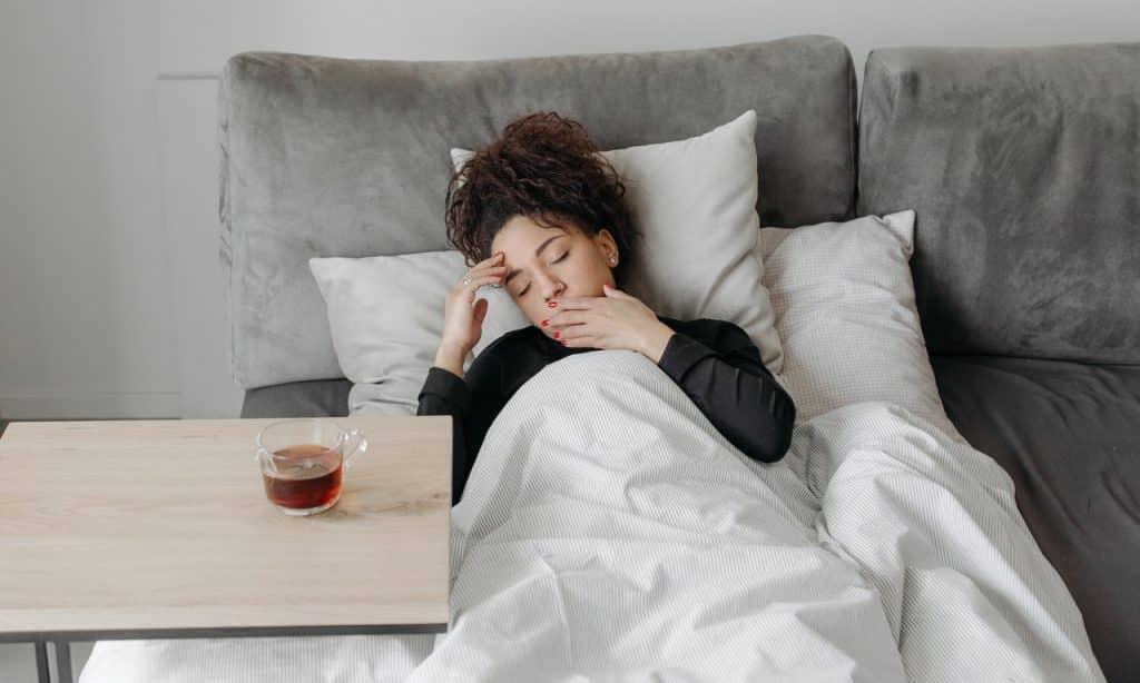 Mulher deitada com os olhos fechados e as mãos tocando o rosto. Uma xícara contendo líquido escuro está posta sobre uma mesa ao lado dela.