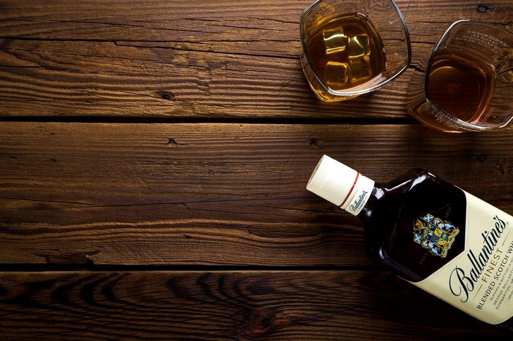 Garrafa de uísque sobre mesa de madeira.