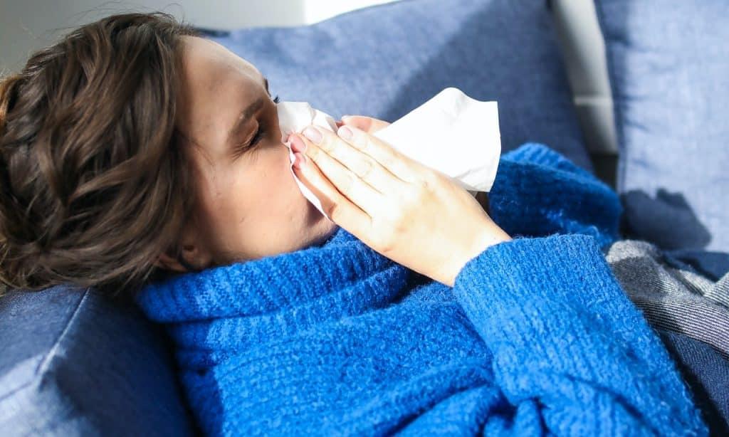 Mulher deitada assoa o nariz.