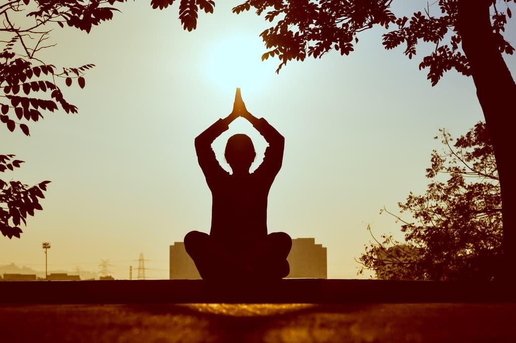 Silhueta feminina praticando exercícios ao ar livre.