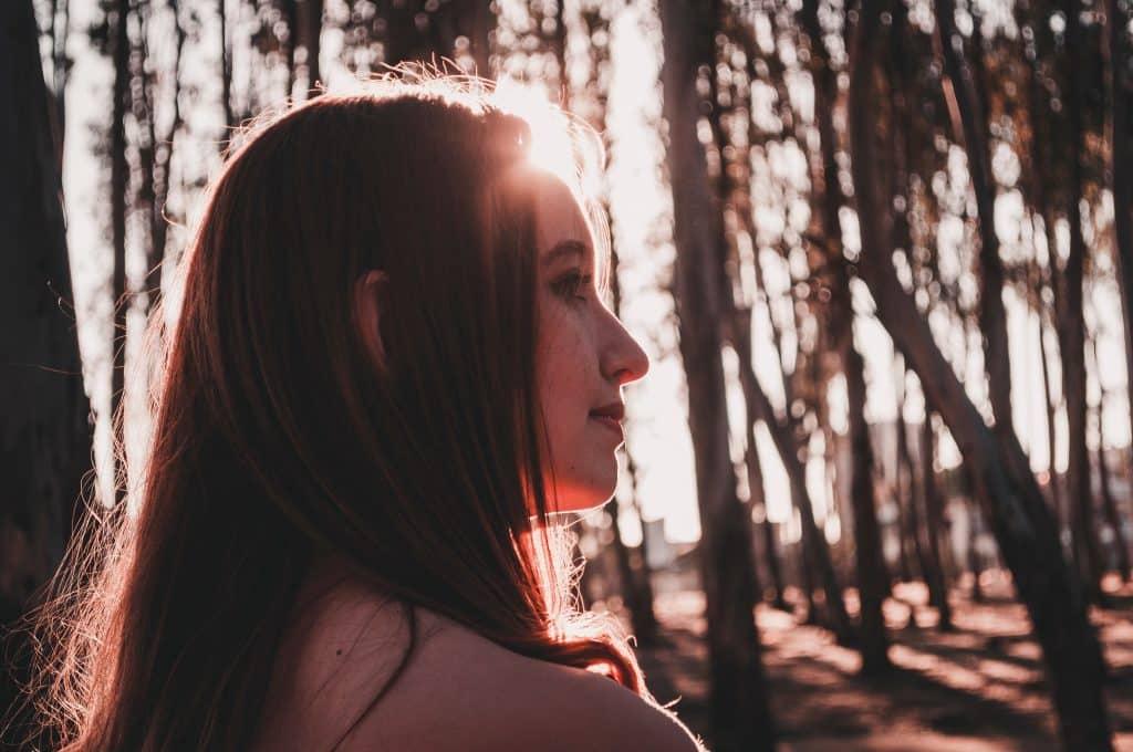 Mulher entre árvores e luz do sol