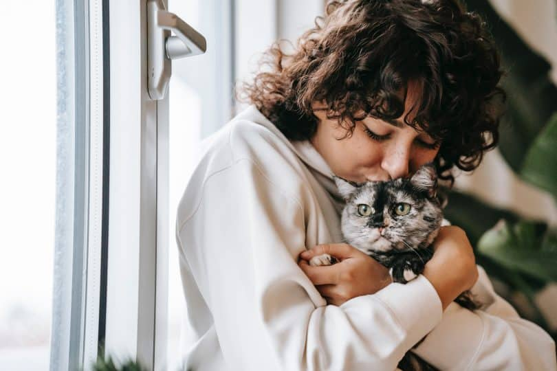 Mulher abraçando e beijando gatinho