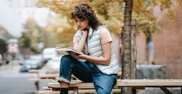Mulher negra sentada numa mesa lendo um livro.