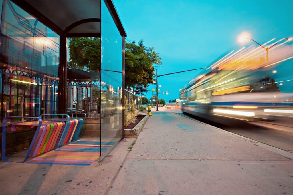 Ponto de ônibus. À direita, há um ônibus em movimento.