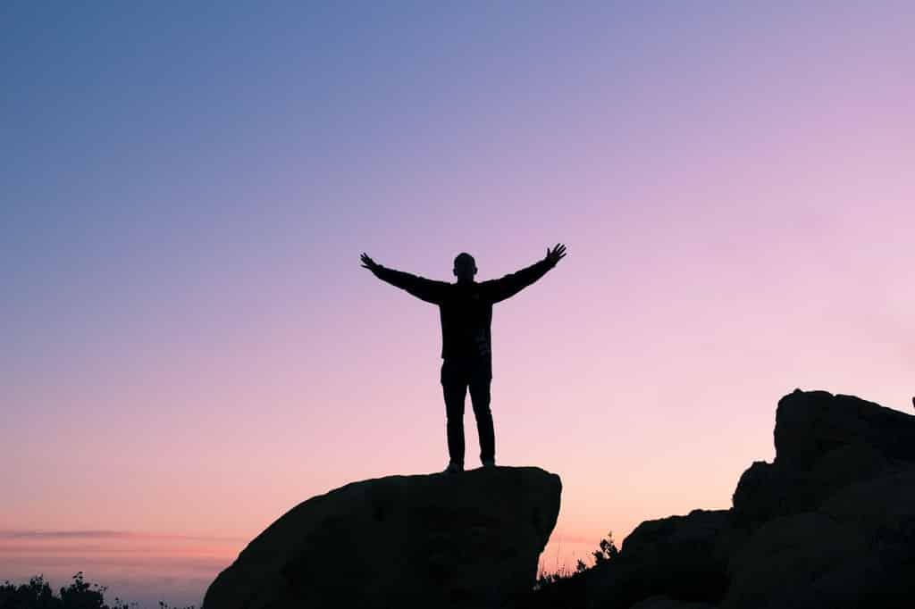Silhueta de homem com os braços erguidos. Ele está de pé sobre uma pedra.
